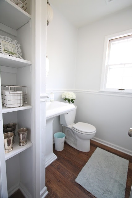 A bathroom with wooden floors and white walls.