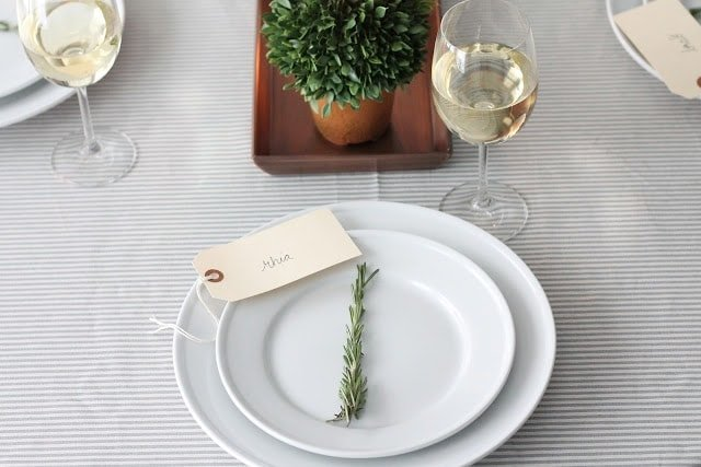 A wooden tray with a candle and a plant on it on a set table.