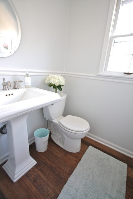 A bathroom with white appliances and white walls, as well as wooden floors.