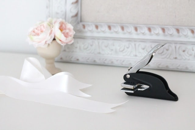 A ribbon and stapler on aa white surface.