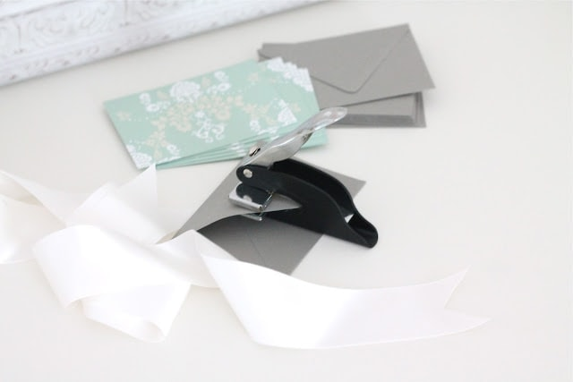 Cards, envelopes, ribbons, and a hole puncher on a white surface.