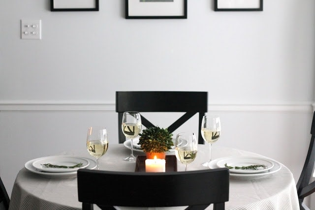 A set table with white plates, wine glasses, a small plant, and a candle in the middle.