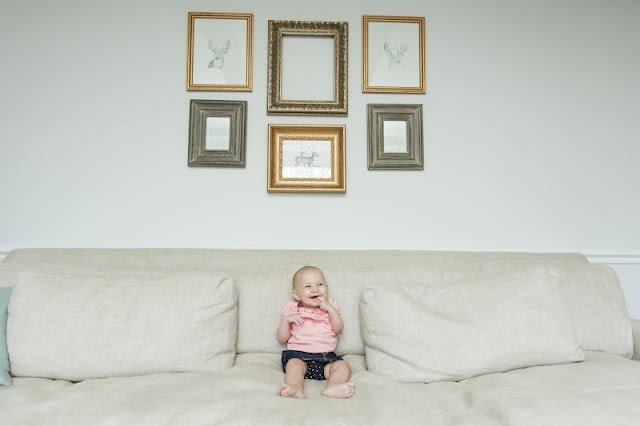 A baby sitting on a couch under a diy gallery wall.