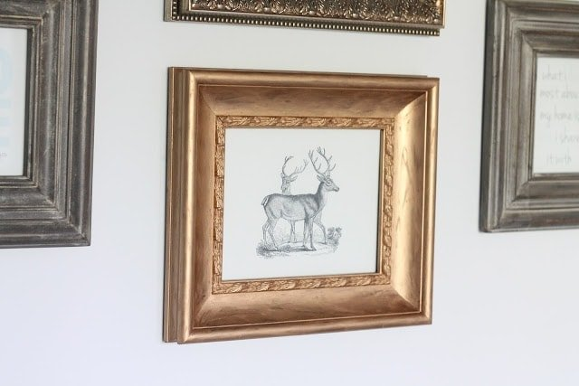 DIY gold gilded frames in a gallery wall over a sofa.