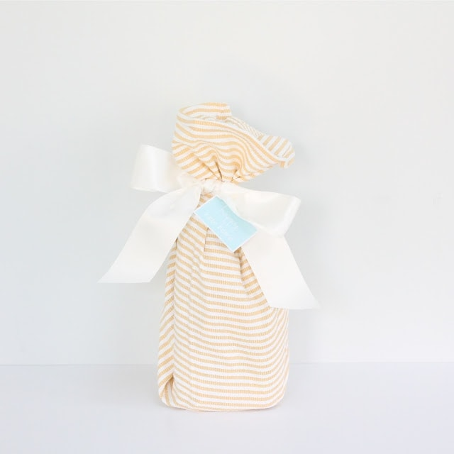 A wrapped gift with a white ribbon and a \'happy new home\' tag.