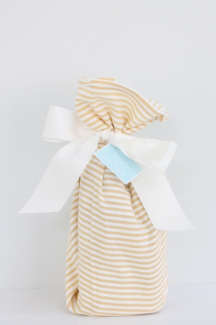 A gift wrapped with a white ribbon and a \'happy new home\' tag.