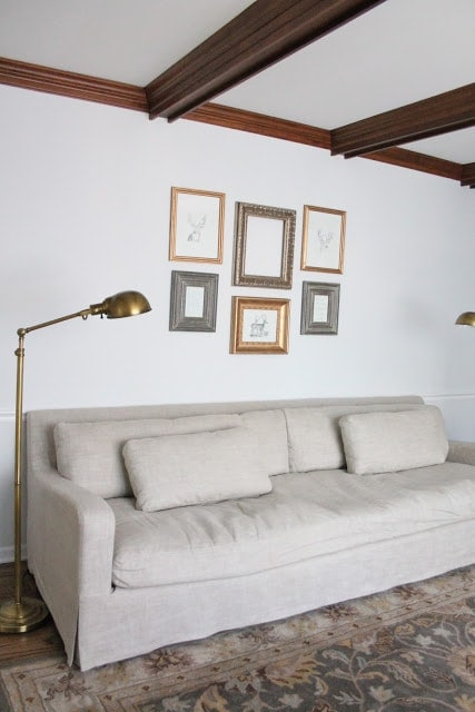 A gallery wall full of a variety of gold gilded frame over a linen sofa.