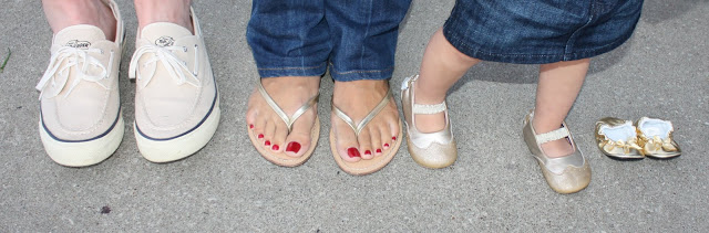 A family\'s feet all next to each other, with an empty pair of baby shoes to the side.