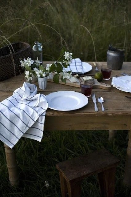 wood table outside in grassy area set with flowers