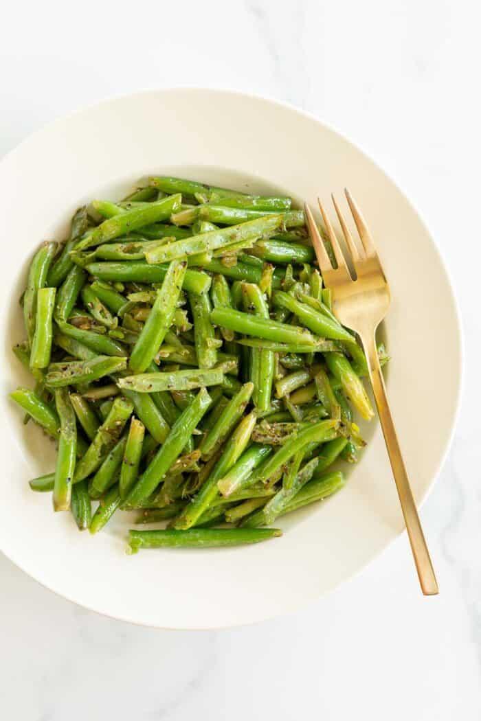 A white bowl full of seasoned green beans, gold fork for serving.