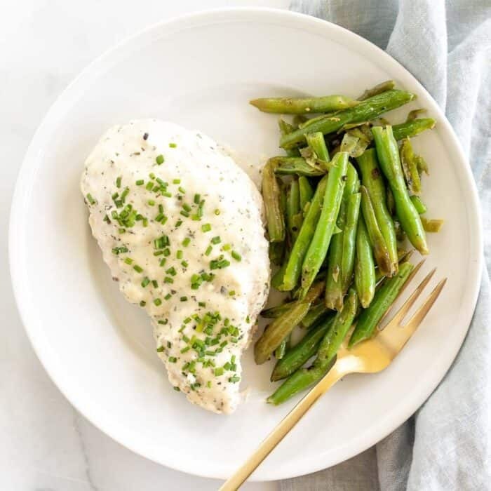A seasoned chicken breast and seasoned green beans on a white plate with gold fork.