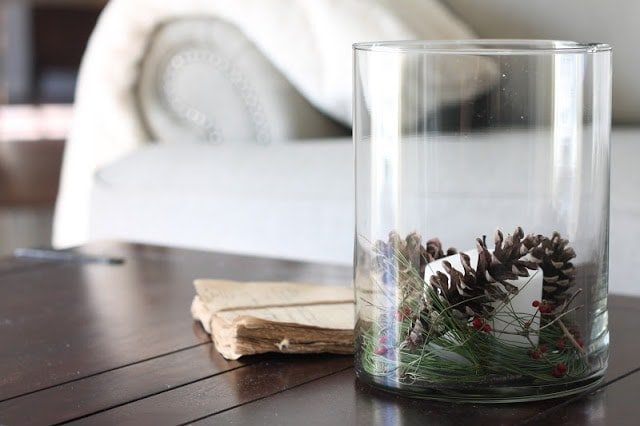 A glass vase of pinecones and christmas greenery on a coffee table.