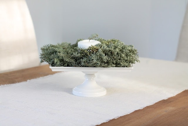 A cake stand of christmas garland and a candle on a dining room table.