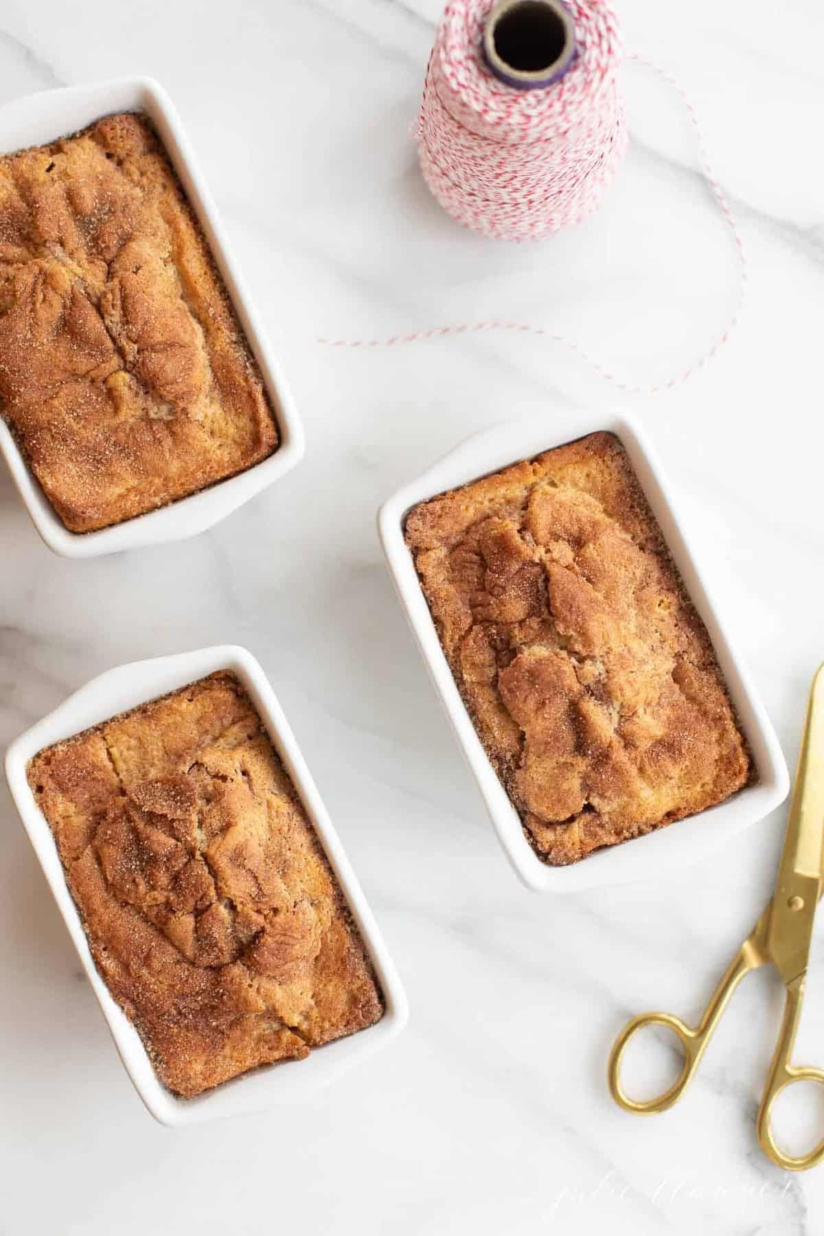 3 cinnamon bread loaves in white miniature loaf pans with red bakers twine and gold scissors