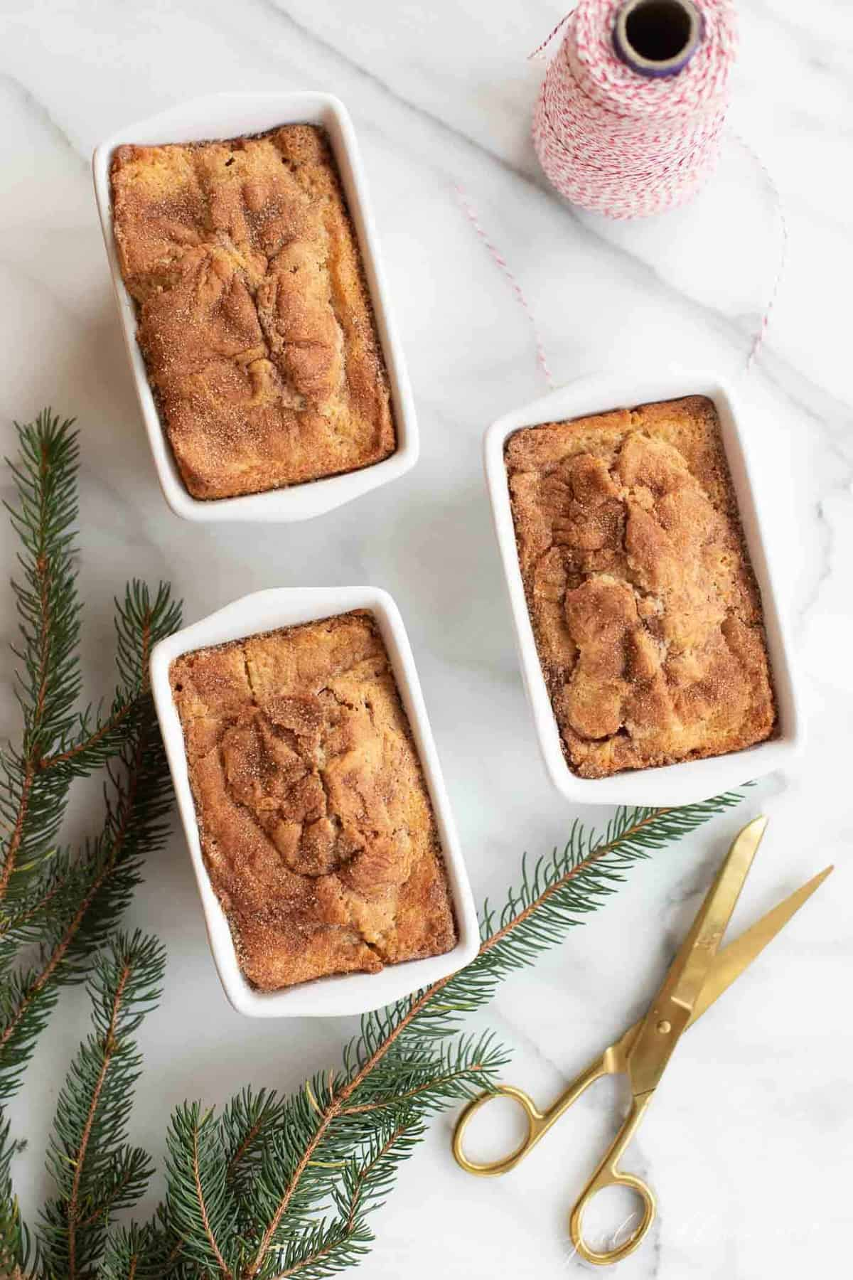 cinnamon bread in white loaf pans by christmas greenery gold scissors and red bakers twine