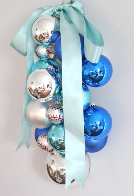 Blue, silver, and baseball ornaments hanging with a blue ribbon
