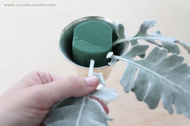 Green leaves being stuck in floral foam
