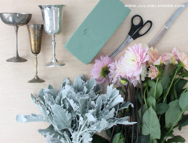 Vases, floral foam, leaves, flowers, and scissors on a wood table.