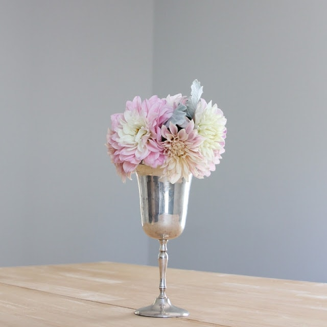 A silver vase with pink and white flowers on a table.