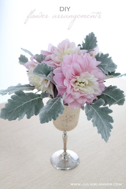A vase filled with leaves and pink and white flowers