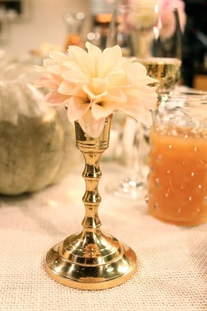 A close up of a gold vase with a light pink flower inside.
