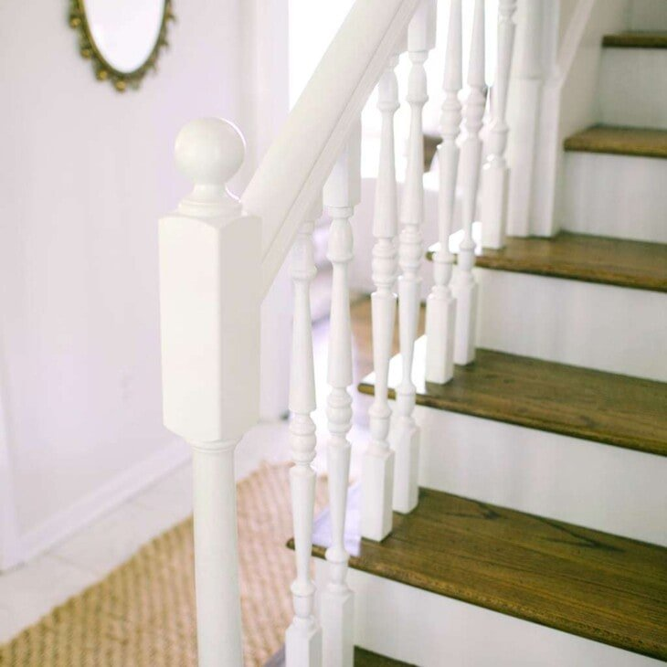 White stairs with wooden tops and white hand railings.