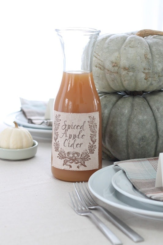 apple cider with fabric label in front of stacked pumpkins
