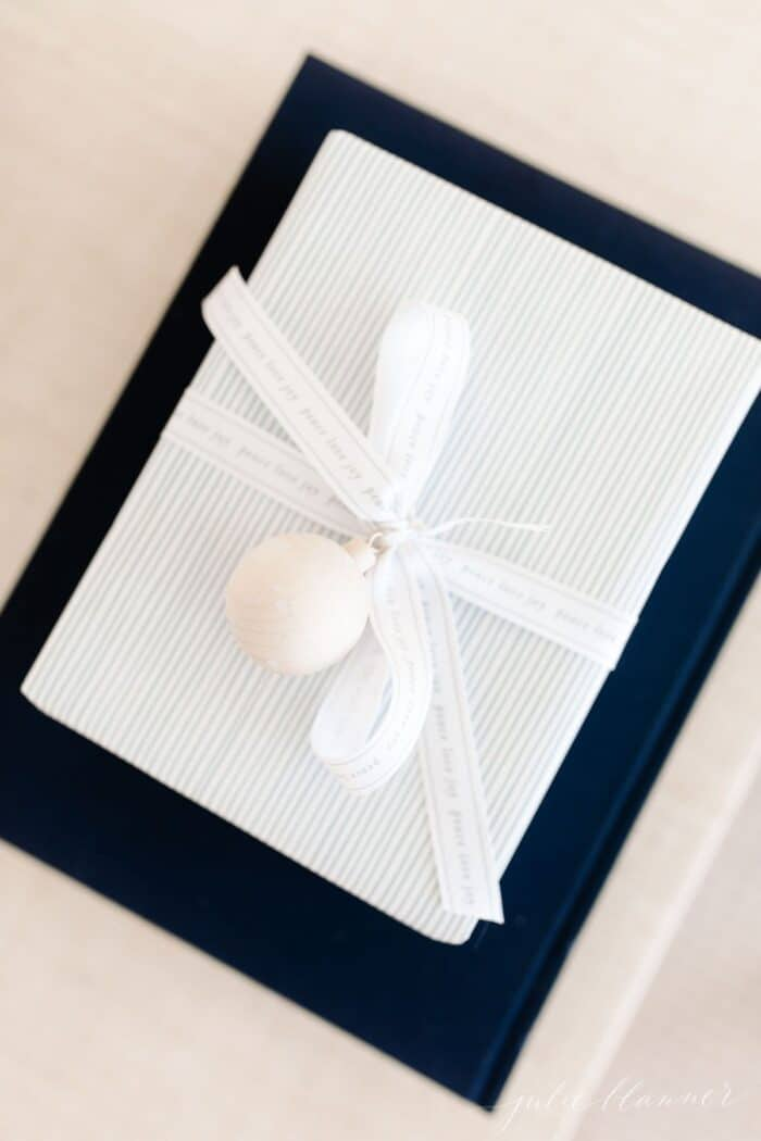 A blue and white christmas gift wrapping box tied with a bow, on top of a navy blue book.