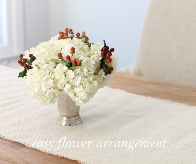 A white centerpiece with red berry accents on a white table runner, which is on a wooden table.