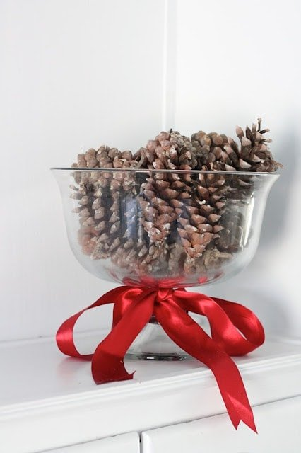 Pinecones in a glass jar with ribbon tied around it.