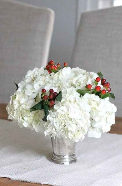 A far shot of white flowers with berry accents in a small vase on a wooden table.