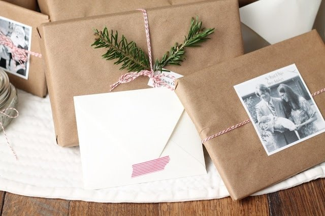 Brown kraft paper wrapped presents tied with baker\'s twine and decorated with old family photos and holiday greenery.