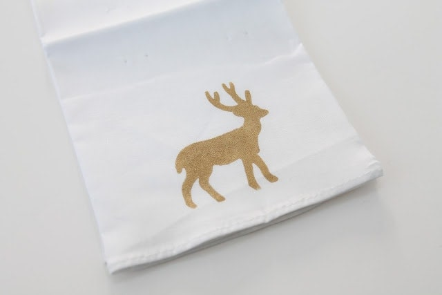 A white napkin with a gold deer tied