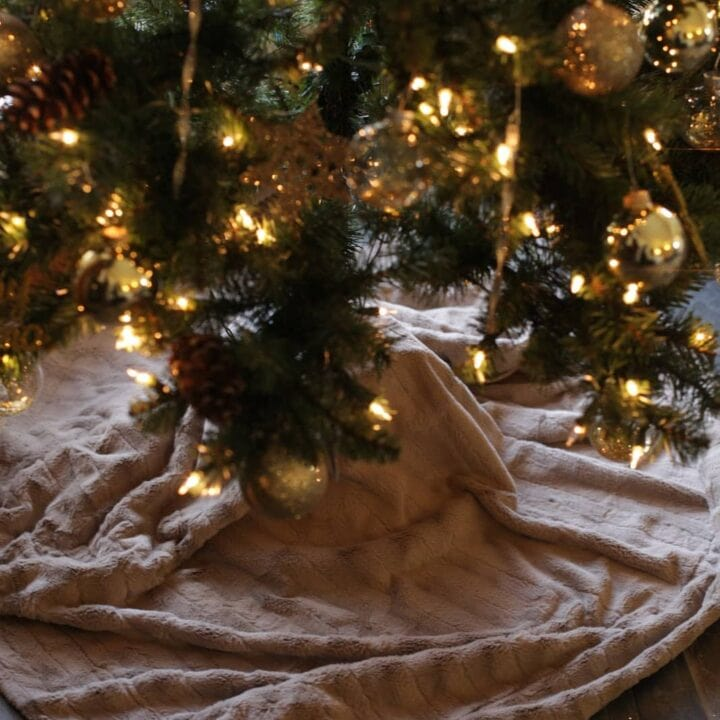 no sew faux fur tree skirt wrapped around the base of a beautifully decorated Christmas Tree