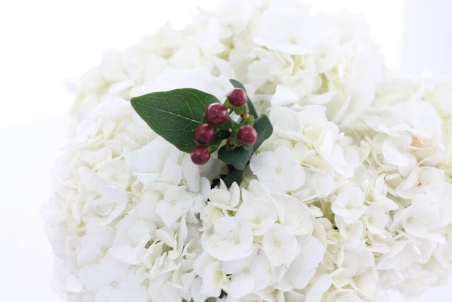 Red berry accents in a bouquet of white flowers.