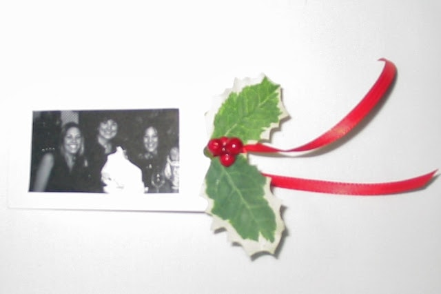 A photo embellishment for Christmas gift wrap with a red ribbon.