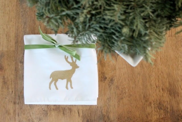 A white napkin with a gold deer tied with green velvet ribbon.