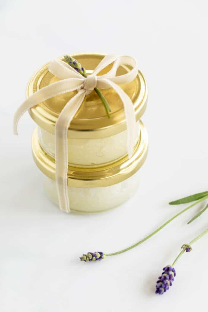 Two small glass bottles with gold lids full of sugar scrub, tied with a bow, fresh lavender in foreground.