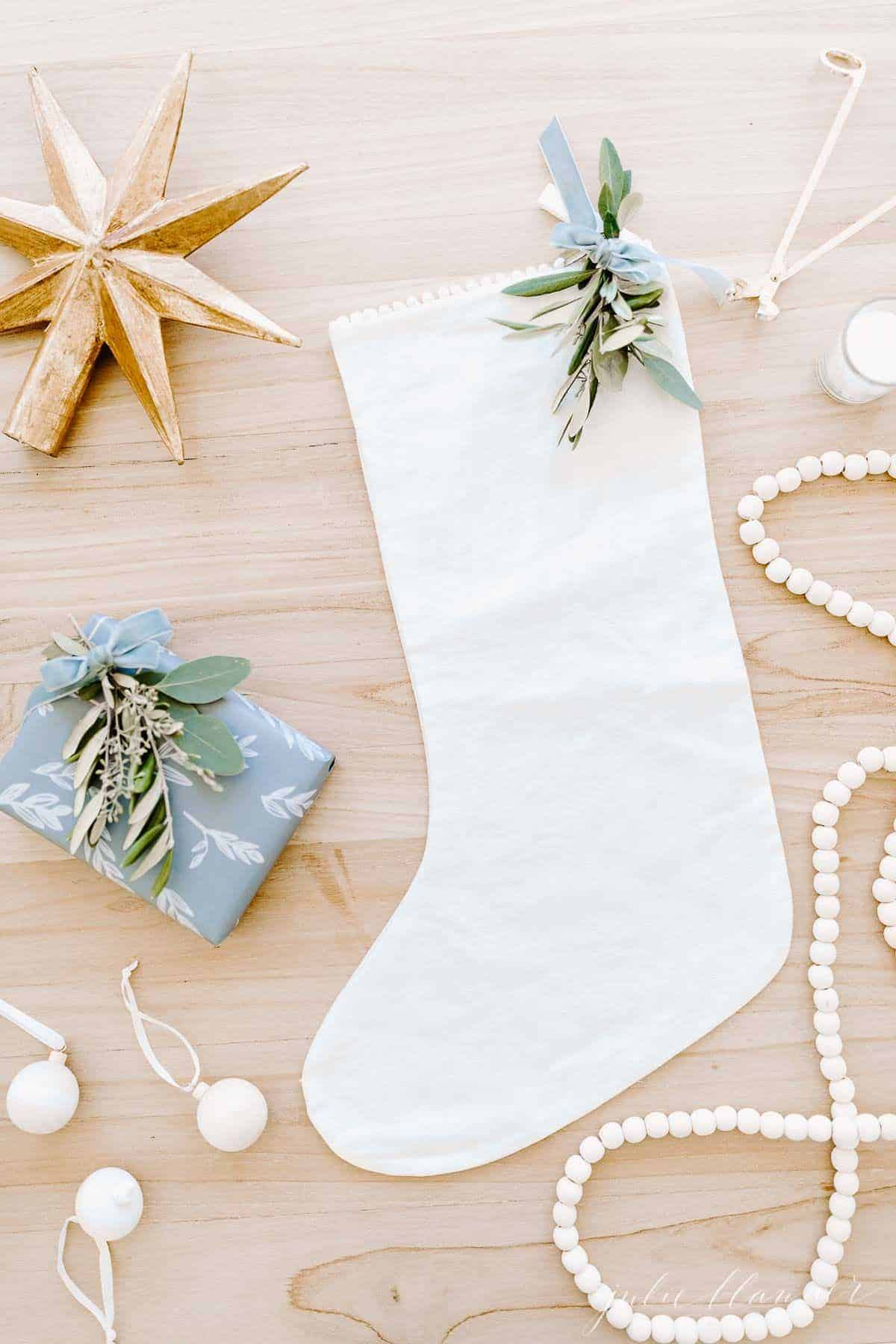 A wooden surface with a linen stocking, a gift card in a blue wrapped box, and wooden Christmas ornaments surrounding.