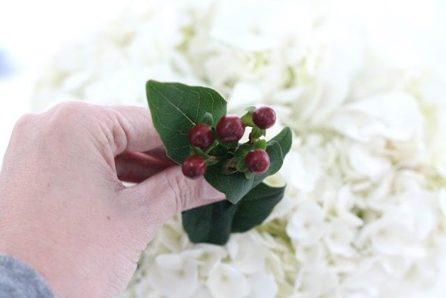 A person holding red berry accents to put into white flowers.