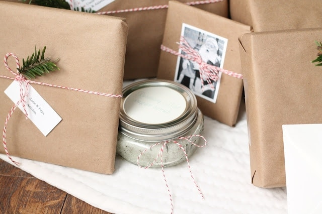 Brown kraft paper wrapped presents tied with baker\'s twine and decorated with old family photos.