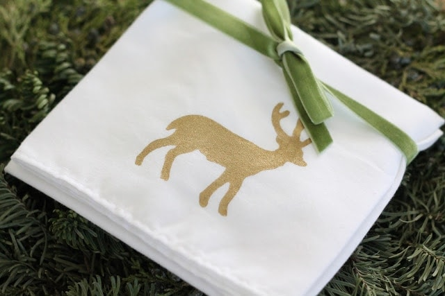 A white towel with a gold deer tied with green velvet ribbon.