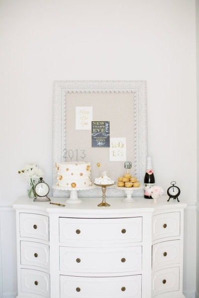 A white table with a pin board above it and a 2013 cake on it.