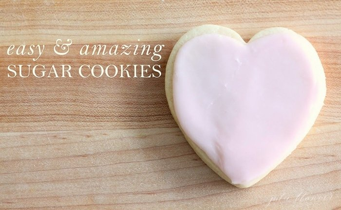 An easy sugar cookie in the shape of a heart with pink frosting, on a wooden surface. Easy & Amazing sugar cookies in a white text overlay.