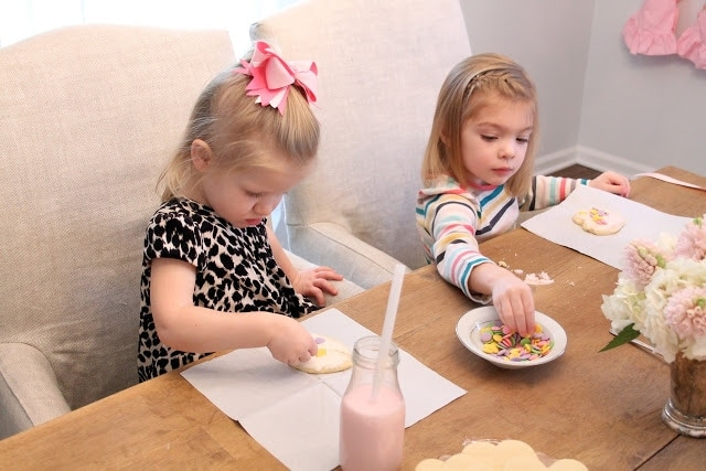 Two little girls decorating cookies