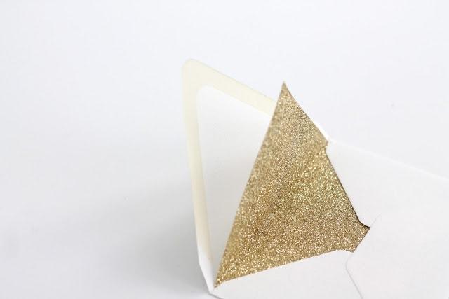 A gold glitter lined envelope