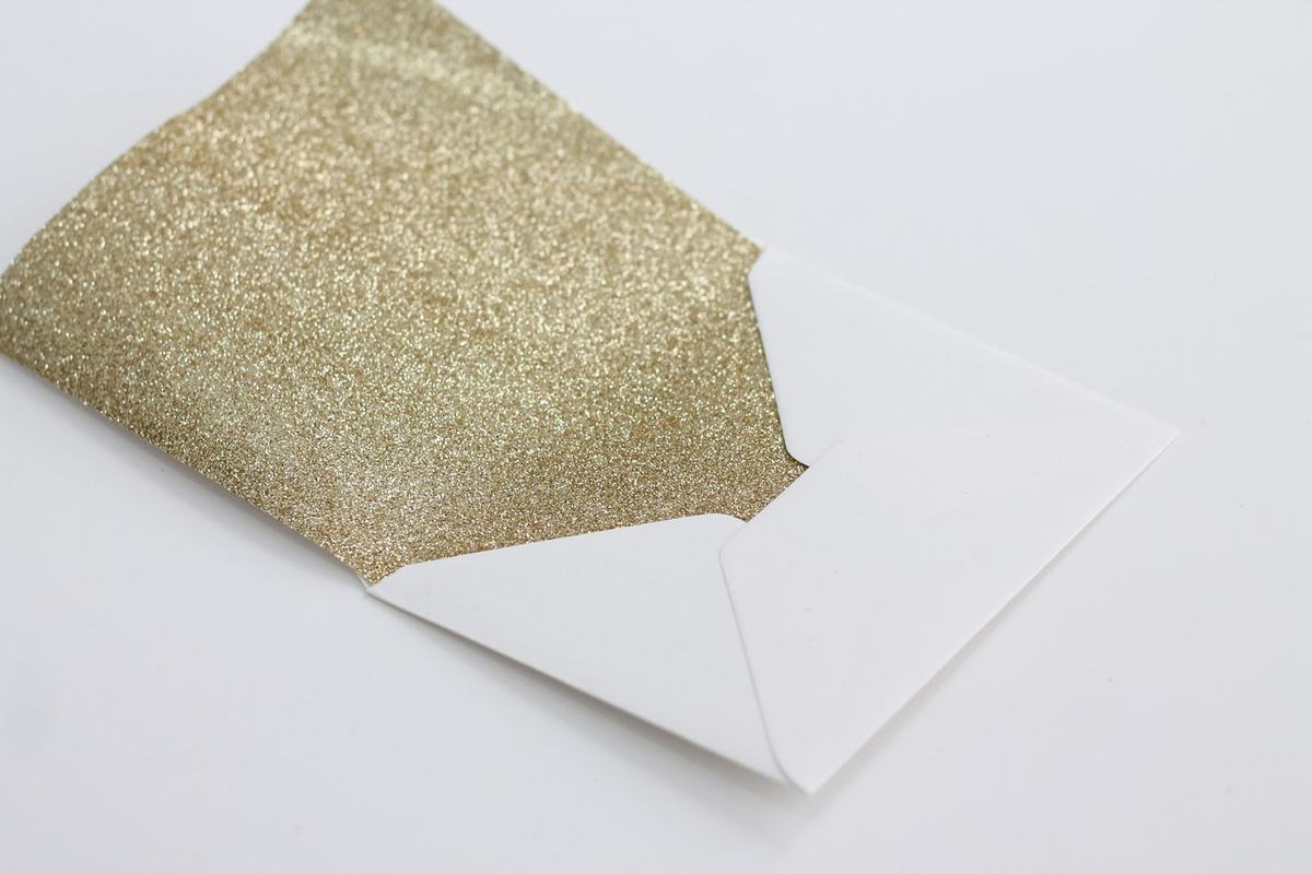 Gold glitter craft paper inserted into white envelope