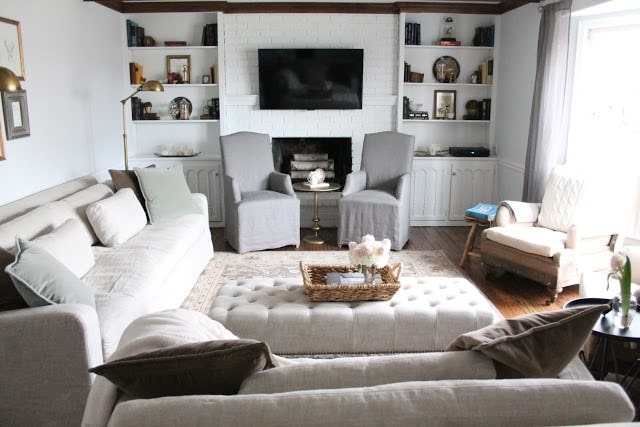 A living room filled with furniture and a fire place. Shelves surround the fire place and a flat screen TV hangs over it as well.