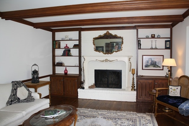 A living room filled with furniture and a fire place. Shelves surround the fire place and mirror hangs over it as well.