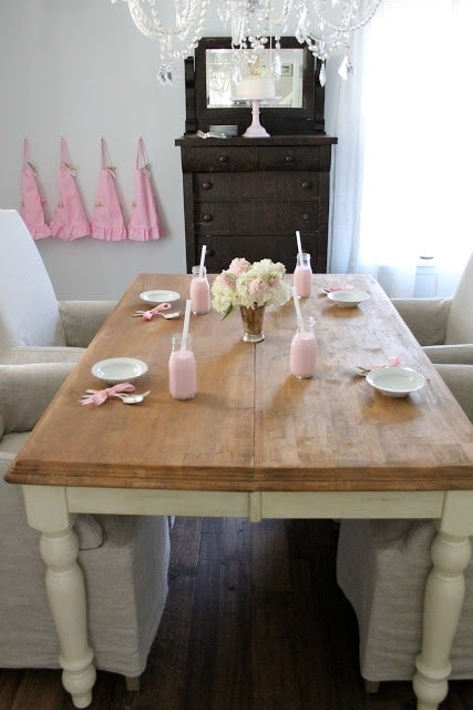 A table set with icing supplies, flowers, and strawberry milk.